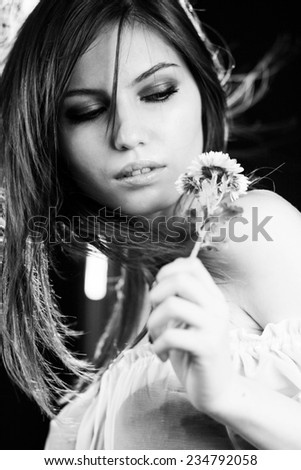 Black and white photo of beautiful caucasian girl posing with dark background