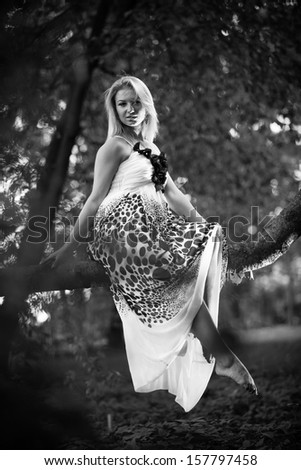Black and white photo of beautiful girl sitting on branch - stock photo