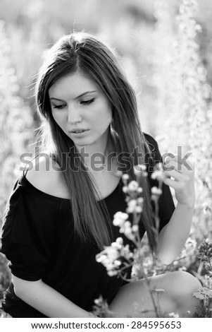 Black and white photo of beautiful girl with long, straight hair posing in the field looking melancholic