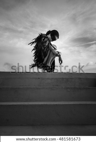 Black and white photo of beautiful seductive angel woman with covered eyes wearing lingerie and leather belts crouching on the roof over cloudy sky