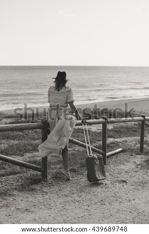 Black and white photo of beautiful woman walking on the road in hat, holding suitcase. Back view, travel concept