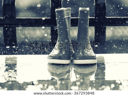 Black and white photo of boots under rain - stock photo