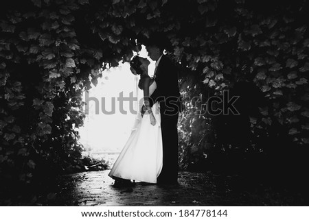 Black and white photo of bride and groom dancing at tree tunnel - stock photo