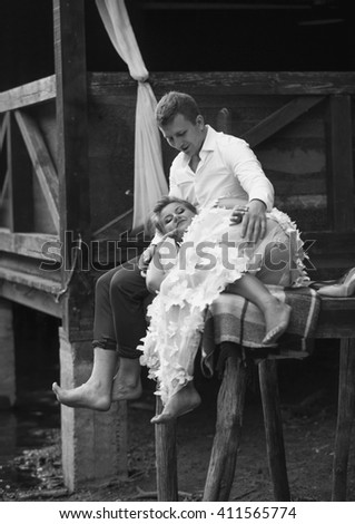 Black and white photo of bride and groom sitting on old wooden pier - stock photo