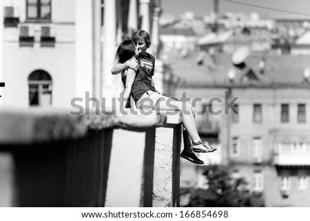 Black and white photo of couple in love sitting on rooftop against city view - stock photo