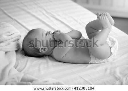 Black and white photo of cute baby in diapers lying on bed - stock photo