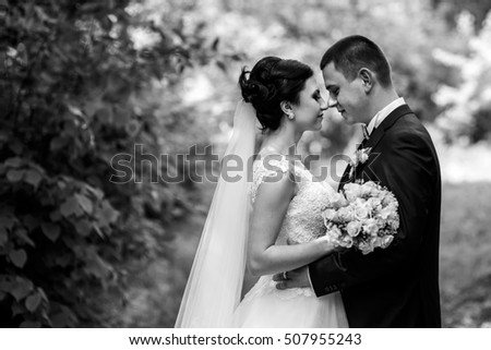 Black and white photo of delightful wedding couple standing in the forest