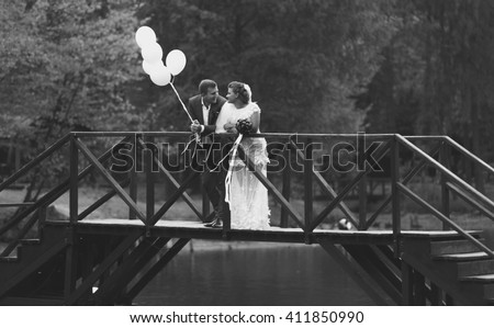 Black and white photo of elegant newlyweds standing on bridge across river