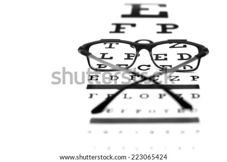 Black and white photo of eye test chart and eye glasses. Studio shot.  - stock photo