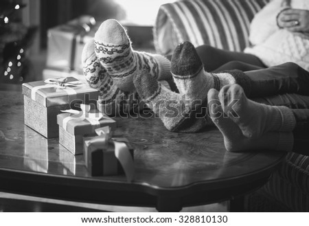 Black and white photo of family warming feet at fireplace - stock photo