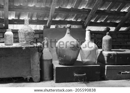 Black and white photo of glass, wooden and metallic objects in the attic with dust and spiderwebs in a beautiful, moody light