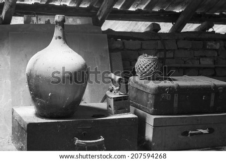 Black and white photo of glass, wooden and metallic objects in the attic with dust and spiderwebs in a beautiful, moody light  - stock photo