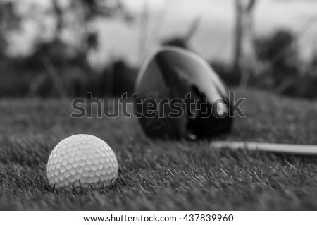 Black and white photo of golf clubs and a golf ball in low light - stock photo