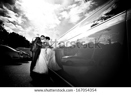 Black and white photo of groom and bride kissing near limousine - stock photo