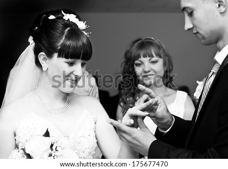Black and white photo of Groom putting a wedding ring on bride's finger - stock photo