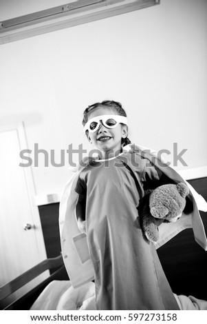 Black and white photo of little girl superhero playing with teddy bear in hospital