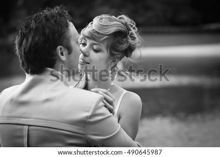 Black and white photo of lovely bride trying to kiss her groom