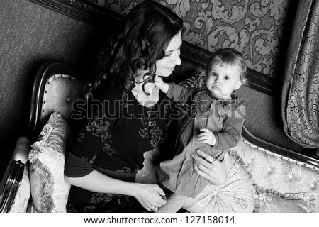 Black and white photo of Loving mother holding her infant baby in classic room - stock photo
