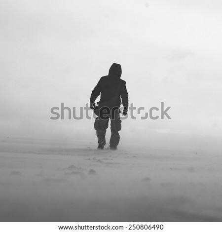 Black and white photo of man in snow storm - stock photo