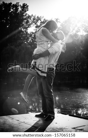 Black and white photo of man lifting up his girlfriend - stock photo