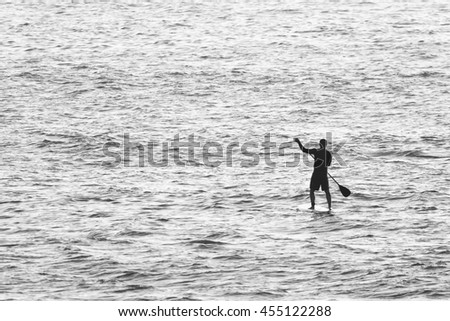 Black and White photo of man on Stand Up Paddle Board surrounded by sea water.
