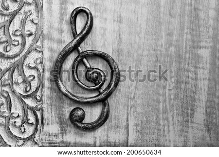 Black and white photo of metal treble clef on distressed wood with decorative carved border.   Closeup with copy space.