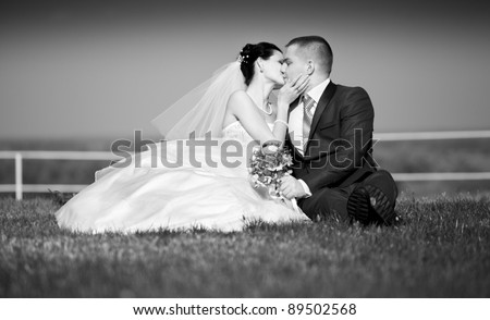 Black and white photo of newly married couple sitting and kissing on lawn - stock photo