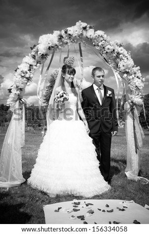 Black and white photo of newly married couple standing under arch - stock photo