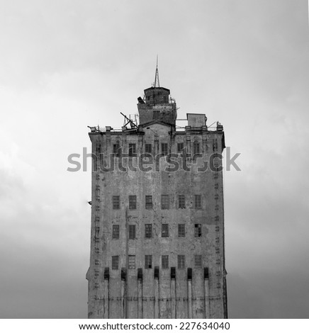 Black and white photo of old building on background of the sky. - stock photo