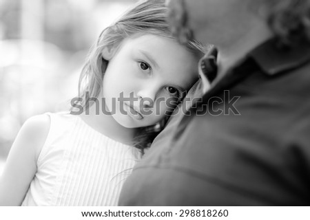 Black and white photo of sad little girl with her father - stock photo