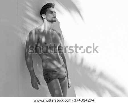 Black and white photo of sexy model in beach shorts - stock photo