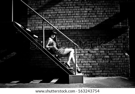 Black and white photo of sexy woman lying on stairs at backyard of building - stock photo