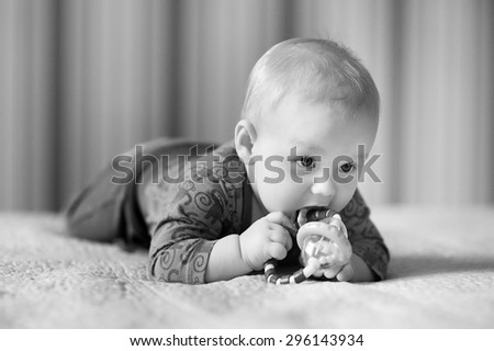 Black and white photo of six month old baby play with toys - stock photo