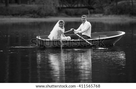 Black and white photo of smiling bride and groom riding on old boat - stock photo
