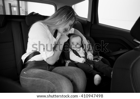 Black and white photo of smiling mother sitting on car backseat with her baby - stock photo