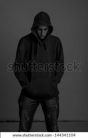 Black and white photo of teenager with hoodie looking down against a dirty gray wall