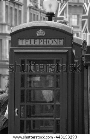 Black and white photo of  telephone box in London with Union Jack flags in the background. British culture