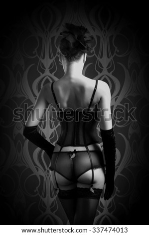 Black and white photo of the beautiful and sexy woman posing in lingerie over dark background