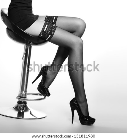 Black and white photo of the beautiful legs in nice stockings over white background - stock photo