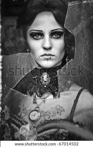 black-and-white photo of the beautiful unusual girl looking through the broken glass - stock photo