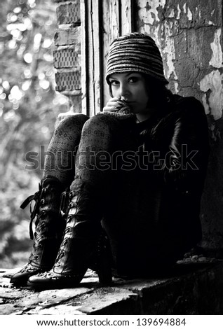 Black-and-white photo of the girl in a retro style sitting on a window sill - stock photo