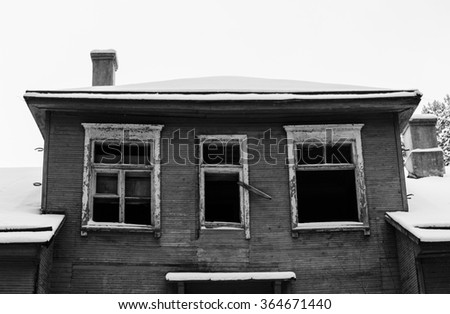 black and white photo of the old abandoned house in snow - stock photo