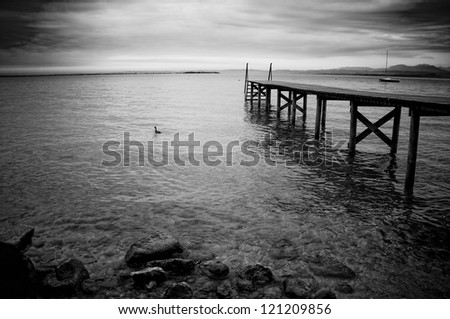 Black and white photo of the wooden jetty on a lake Garda in Italy