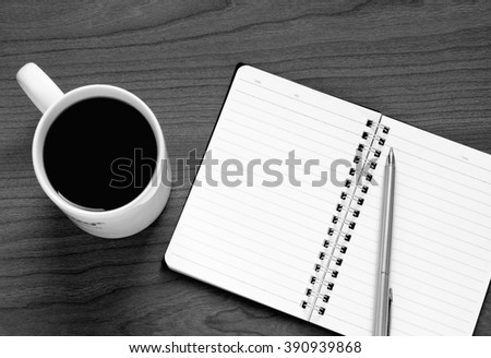 Black and white photo of top view on opened notebook, pen and cup of coffee on wooden office desk. - stock photo