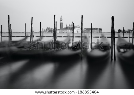 Black and white photo of Venice seafront with gondolas on the waves. Venice, Italy - stock photo