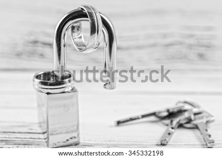Black and white photo of wedding rings on opened shiny padlock and keys. Concept for marriage problems