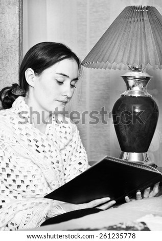 Black and white photo of woman reading a book at lamp - stock photo