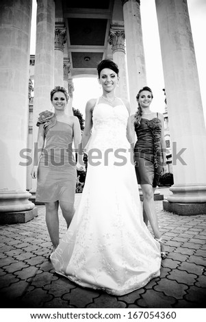 Black and white photo of young bride walking with two bridesmaids against ancient columns - stock photo