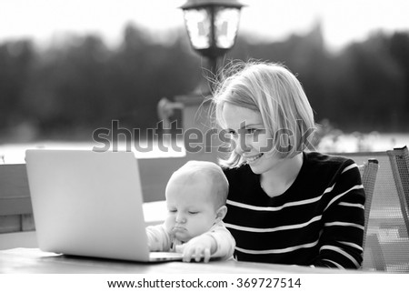Black and white photo of young happy mother with her adorable baby girl working or studying on laptop in outdoor cafe - stock photo