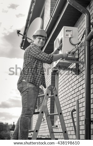 Black and white photo of young man repairing air conditioner standing on ladder - stock photo